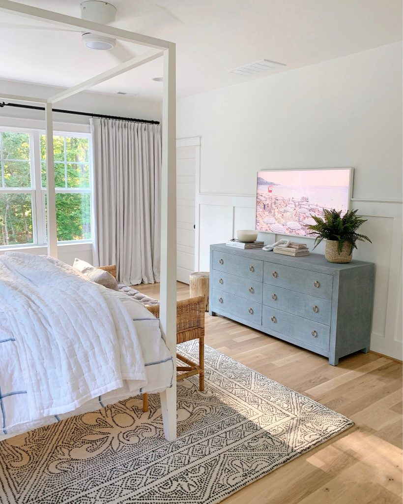 a bedroom with the Frame tv and Gray Malin art