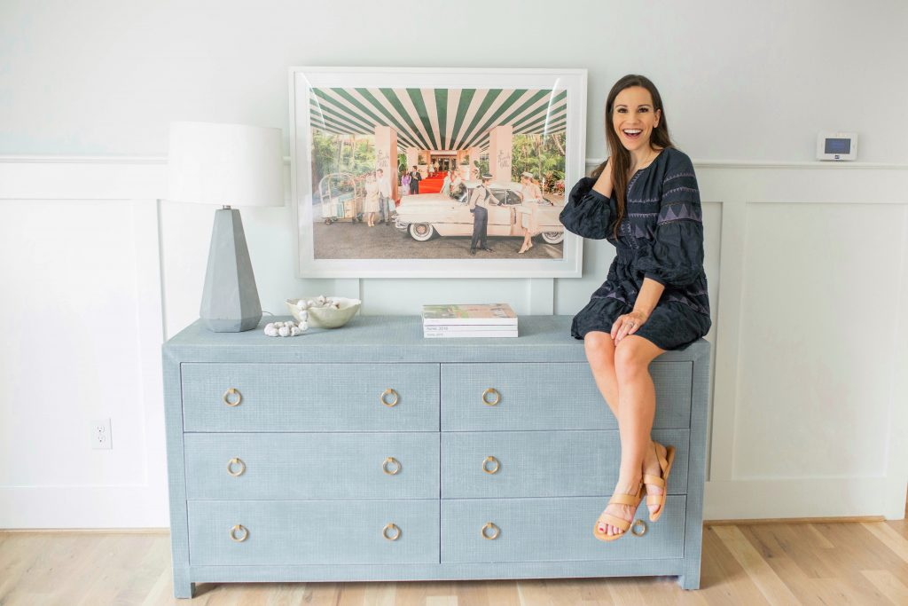 Chrissy Marie Blog in front of Gray Malin print in a bedroom with a blue dresser