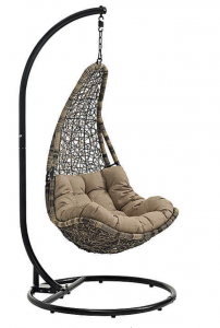 black swinging chair on a sand with a pillow