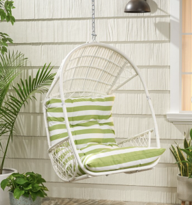 white hanging chair with a green cushion