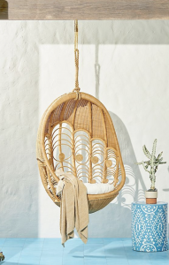 rattan hanging chair with a blue blanket
