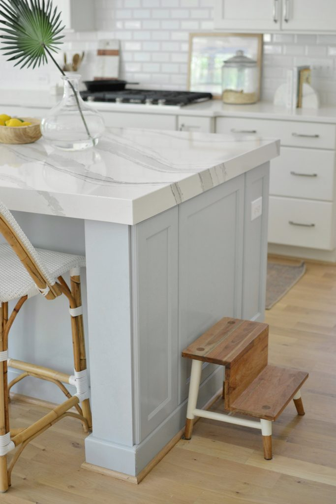 a blue kitchen island with kids step stools
