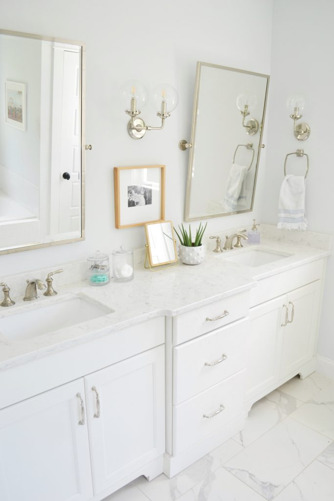 a bathroom vanity with 2 sinks and 2 mirrors