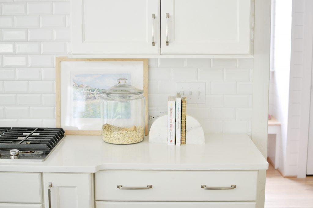 a white kitchen with white subway tile
