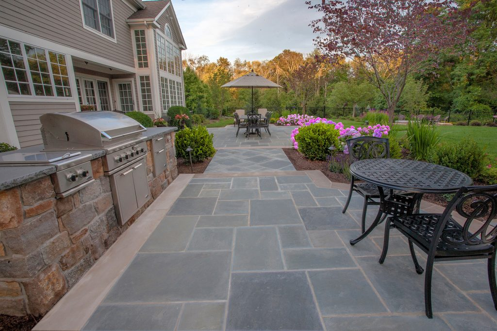 a long outdoor space with bluestone pavers