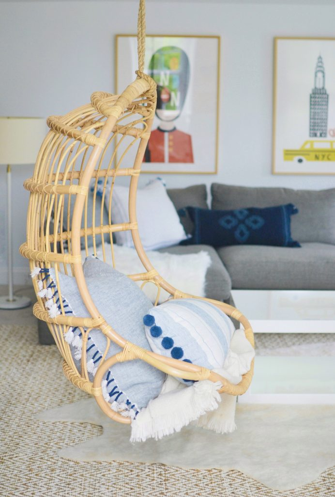 hanging rattan chair with 2 blue pillows