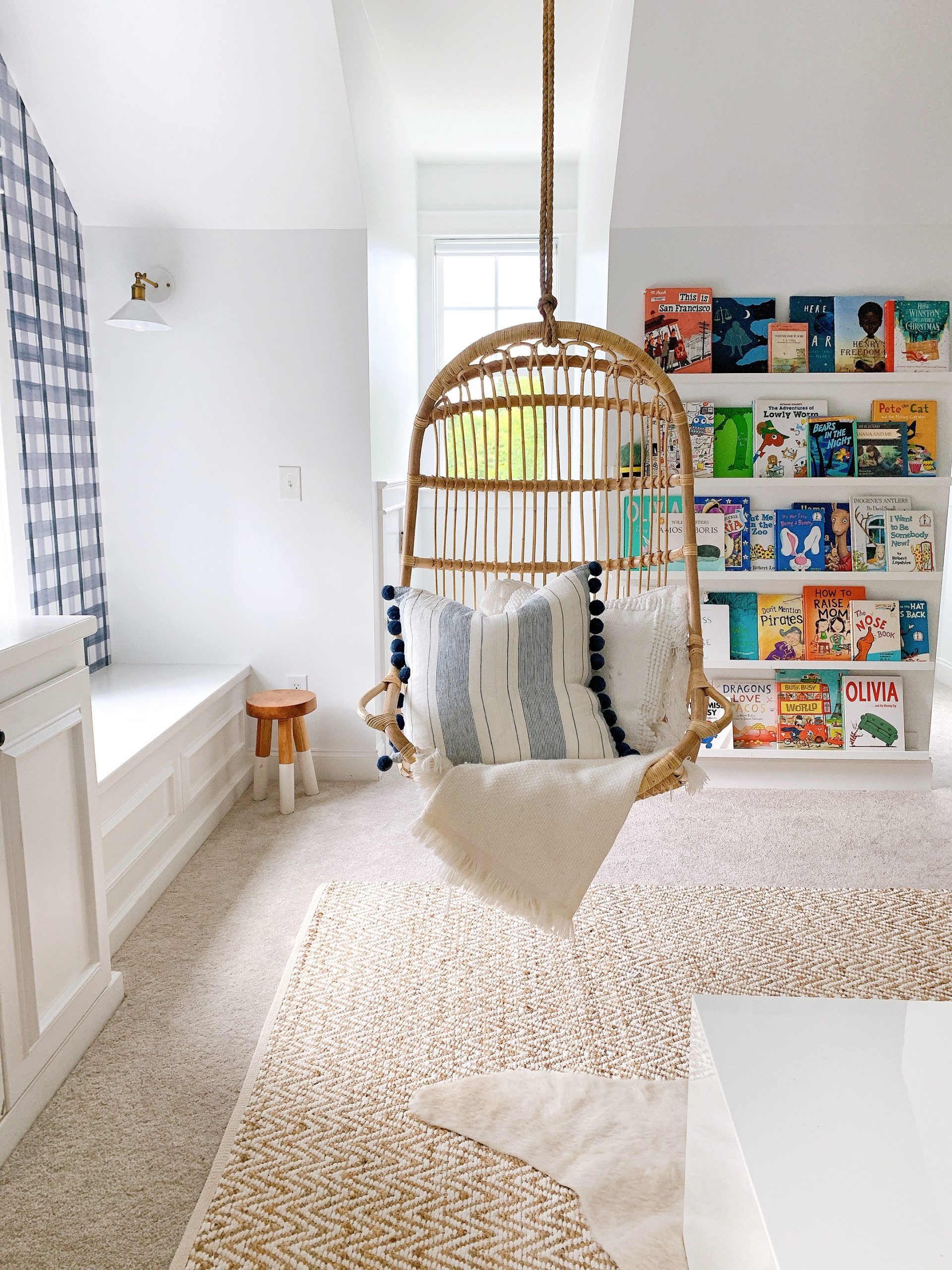 a blue striped pillow in a hanging rattan chair