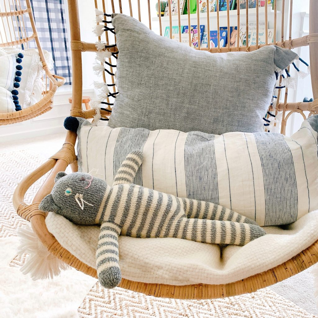 hanging rattan chair with a stuffed animal and pillow in it