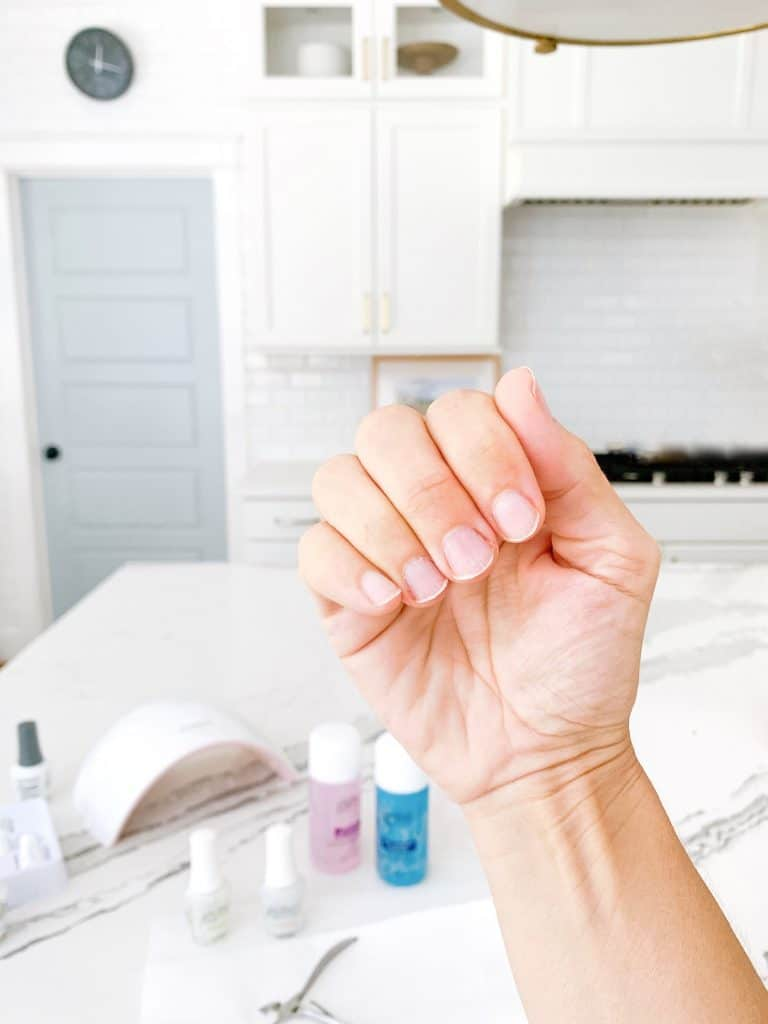 a hand with no gel manicure at home in a kitchen