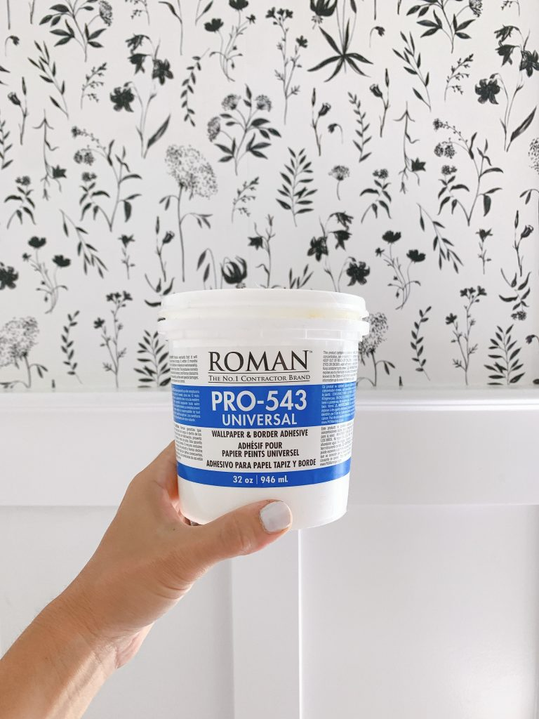 a hand holding up a bucked of Roman pro 543 wallpaper adhesive