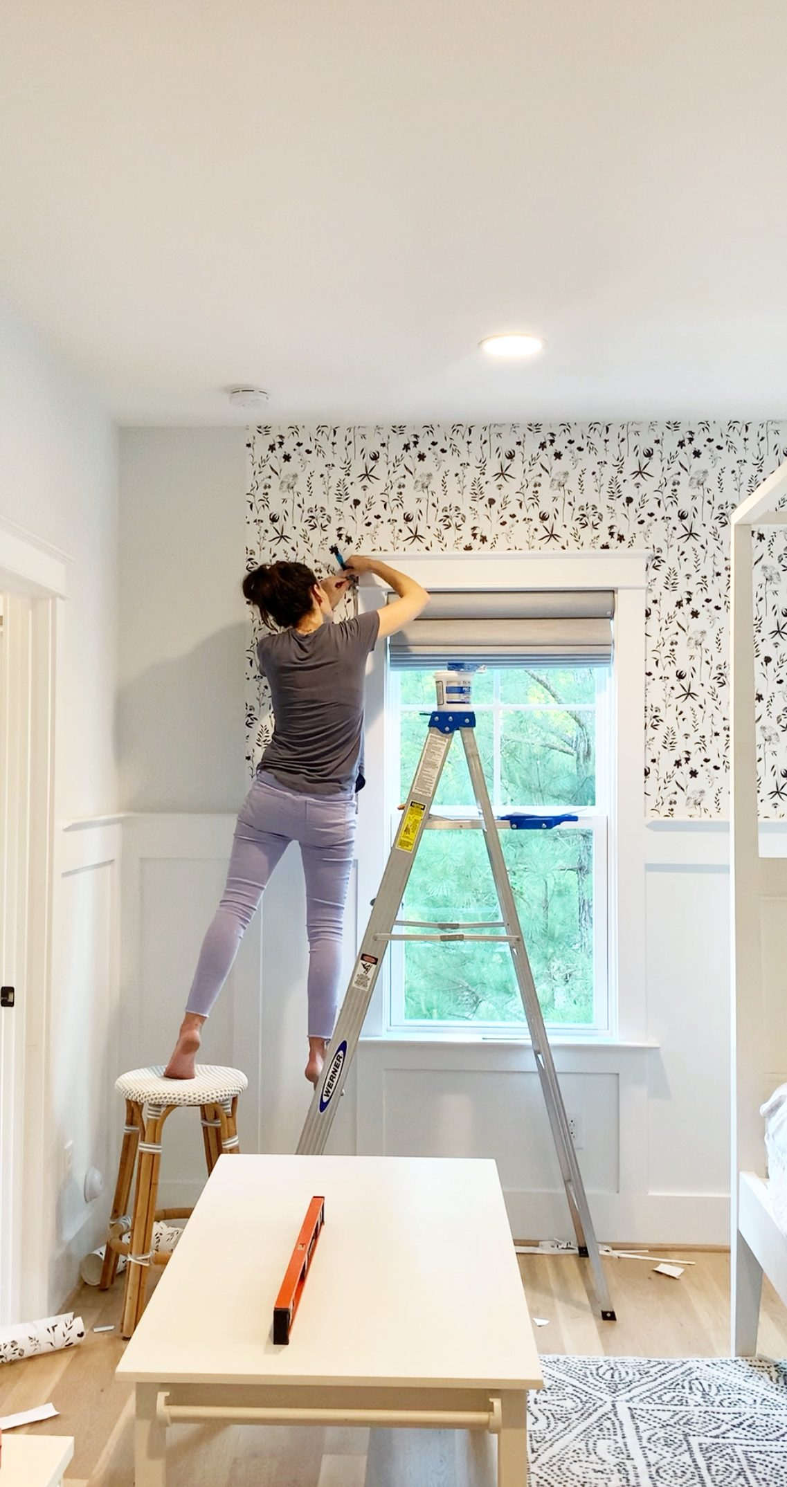 a woman showing how to hang wallpaper in a bedroom