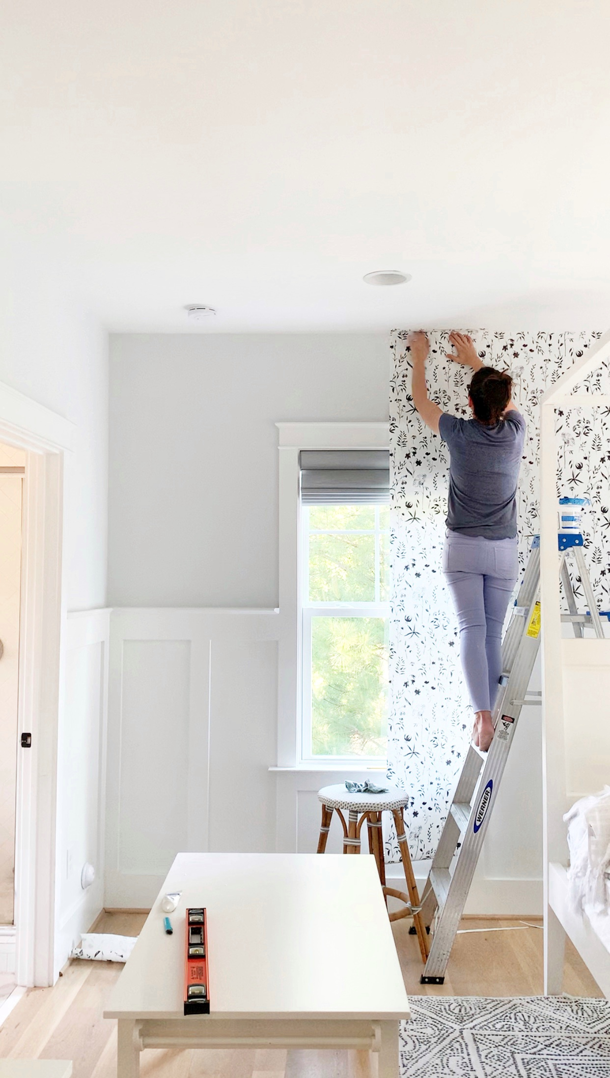 a woman showing how to hang black and white wallpaper