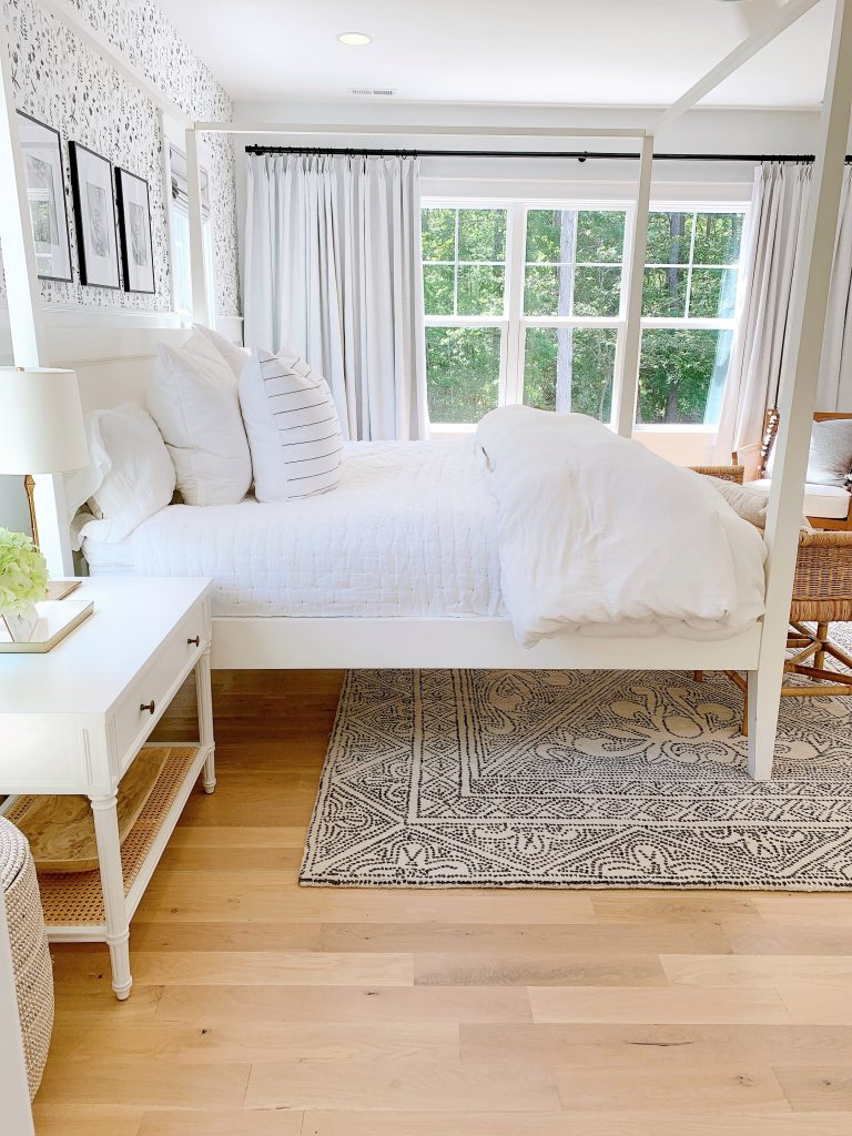 a black and white bedroom with white bedding
